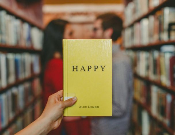 A hand holds a copy of a book titled Happy