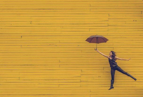 A woman jumps holding an open umbrella