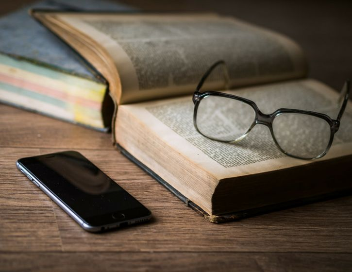 An old book, a pir of glasses and a smartphone