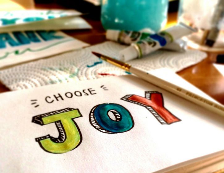 A piece of paper with written choose Joy