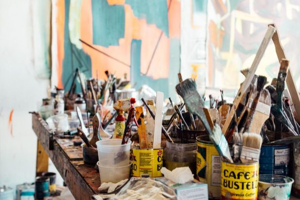 A painter table full of paint brushes, colors and towels