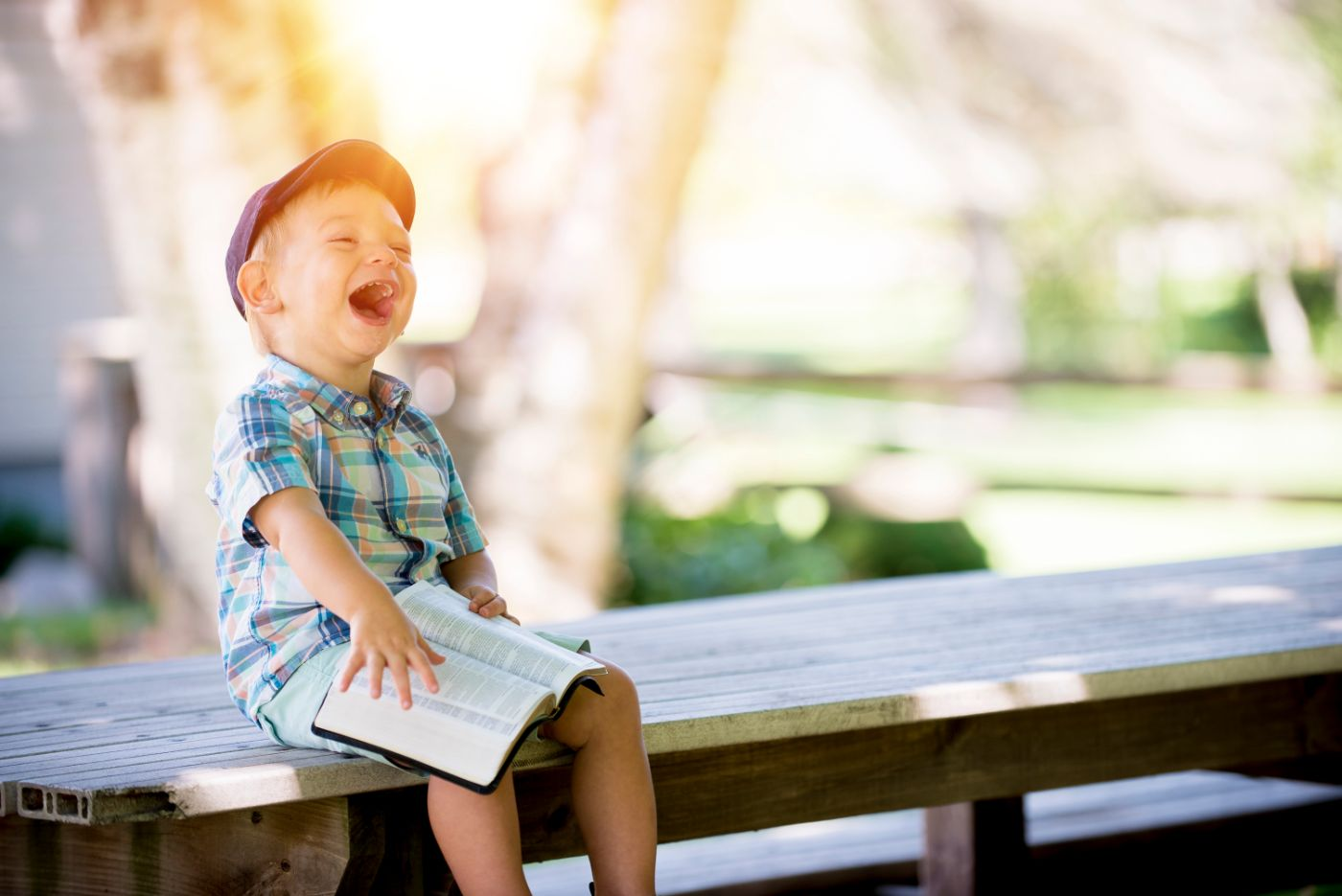 A kid reading and laughing on a bench
