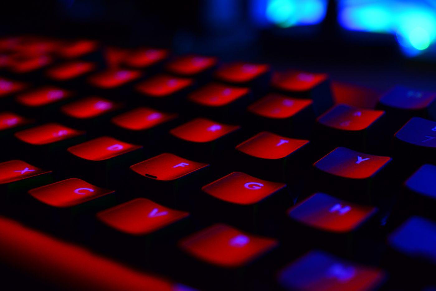 Black keyboard under red and blue lights
