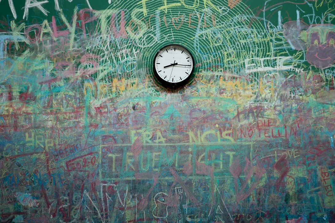 A wall full of graffiti with a clock