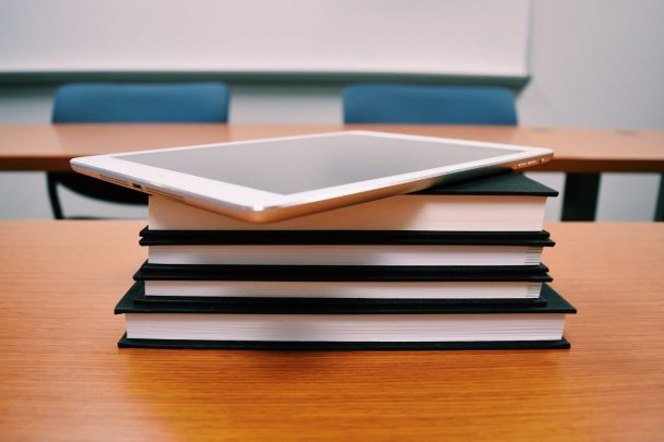 A stack of books with a tablet on top