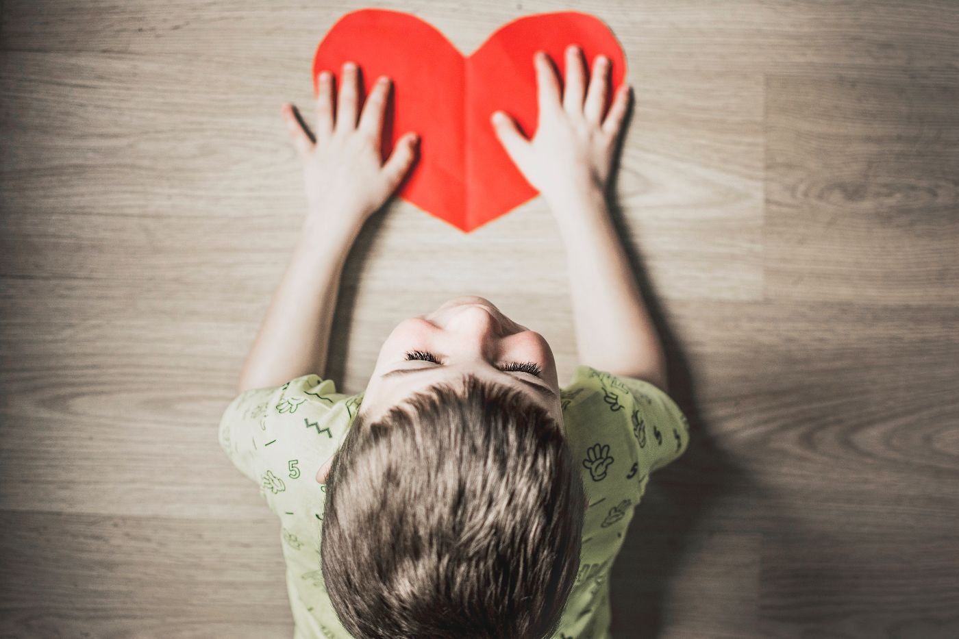 A kid holds a heart shaped piece of paper