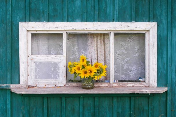 A wooden window with a vase of yellow flowers