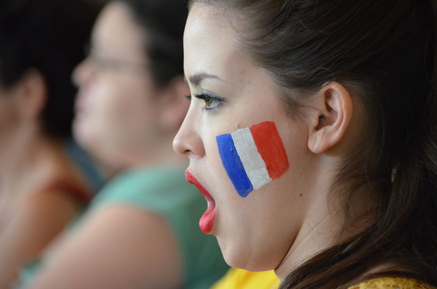 A girl with the french flag painted on her face